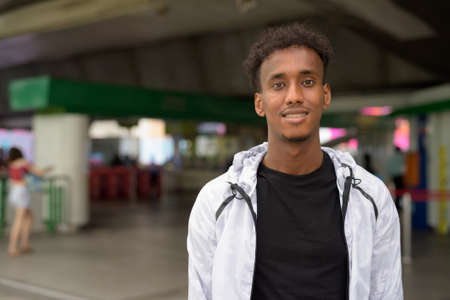 Portrait of handsome black African man smiling at train station 스톡 콘텐츠