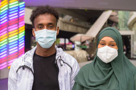 African man and African Muslim woman wearing face mask to protect from virus