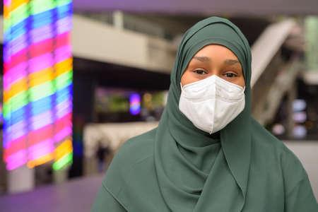 Beautiful black African Muslim woman wearing face mask outdoors