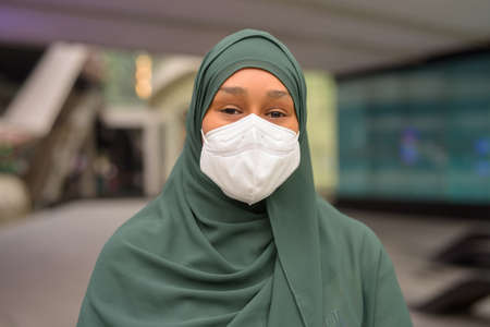 Portrait of beautiful black African Muslim woman wearing face mask outdoors 스톡 콘텐츠
