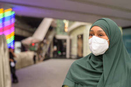Portrait of beautiful black African Muslim woman wearing face mask outdoors while thinking