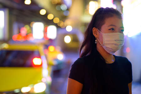 Asian woman wearing face mask to protect from covid 19 outdoors at night while at taxi station Stock Photo