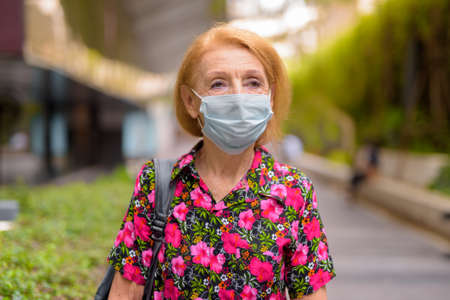 Outdoors portrait of senior tourist woman wearing disposable medical face mask and thinking. Safety in public place during virus outbreak.