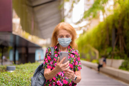 Outdoors portrait of senior tourist woman wearing disposable medical face mask and using mobile phone. Safety in public place during virus outbreak. 免版税图像
