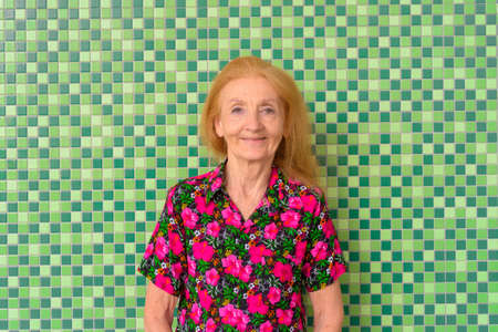 Portrait of a senior woman smiling outdoors during summer against colorful background wall
