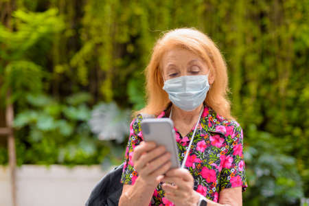 Outdoors portrait of senior tourist woman wearing disposable medical face mask and using mobile phone during summer