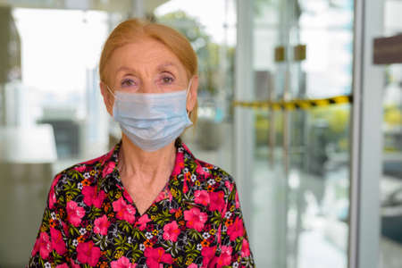 Indoors portrait of senior woman wearing disposable medical face mask against closed gym during virus  pandemic