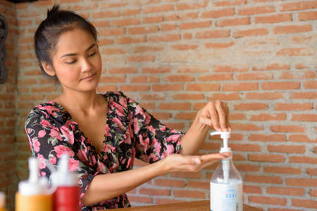 Woman cleaning hands with alcohol gel for protection against virus at restaurant