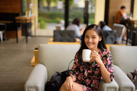 Portrait of beautiful Asian woman smiling and sitting at coffee shop 免版税图像