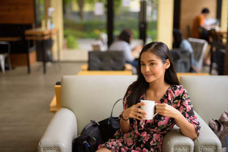 Portrait of beautiful Asian woman sitting and thinking at coffee shop