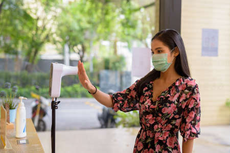 Portrait of woman wearing face mask and measuring body temperature while entering restaurant for protection against virus
