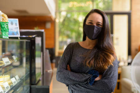 Portrait of confident woman wearing face mask for protection against virus at restaurant