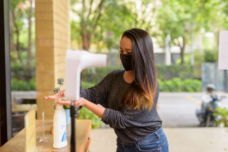Woman washing hands with alcohol gel to protect against virus