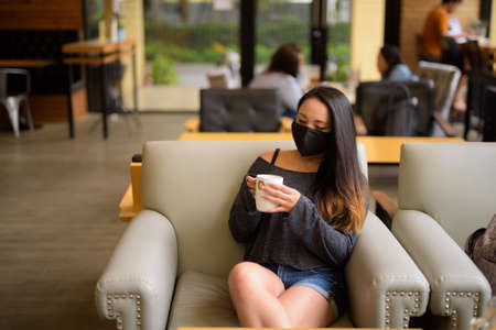 Woman wearing face mask for protection against virus while sitting at coffee shop 免版税图像