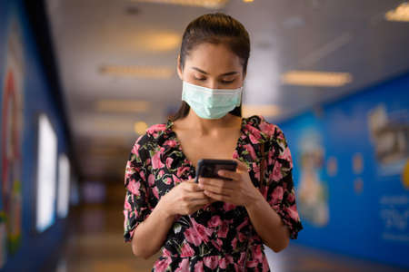 Portrait of woman wearing face mask for protection against virus while using mobile phone