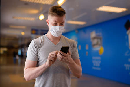 Tourist man wearing face mask for protection against virus while using mobile phone