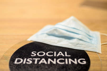 Social distancing text and face mask on table at restaurant