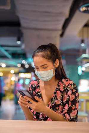 Woman wearing face mask for protection against virus while using mobile phone at restaurant 免版税图像
