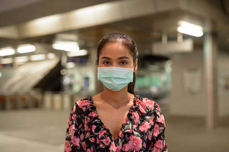 Woman wearing face mask for protection against virus outdoors at night 免版税图像