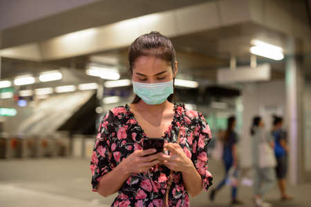 Woman wearing face mask for protection against virus outdoors at night while using mobile phone