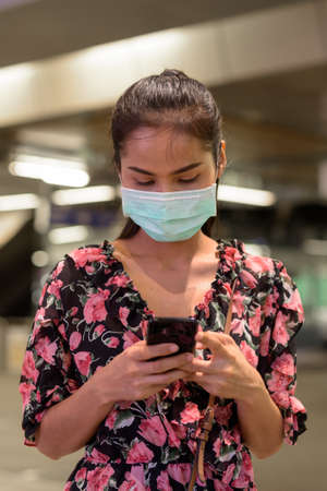 Woman wearing face mask for protection against virus outdoors at night while texting with phone