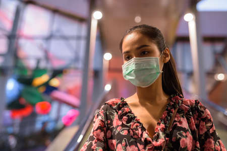 Portrait of woman wearing face mask for protection against virus at escalator outdoors 免版税图像