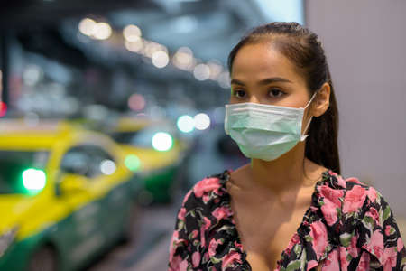 Woman wearing face mask for protection against virus while waiting taxi at night