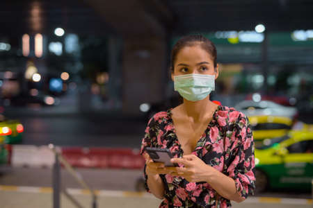 Woman wearing face mask for protection against virus while waiting taxi at night and using mobile phone