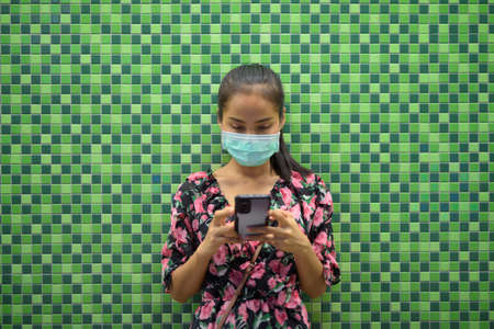 Portrait of woman wearing face mask for protection against virus at night against colorful wall with copy space while texting with mobile phone