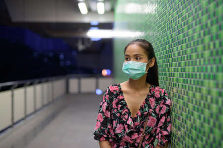 Portrait of woman wearing face mask for protection against virus at night while thinking