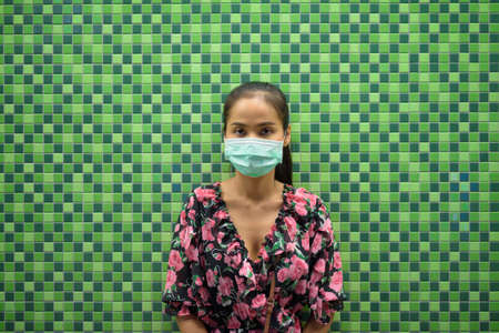 Portrait of woman wearing face mask for protection against virus at night against colorful wall with copy space 免版税图像