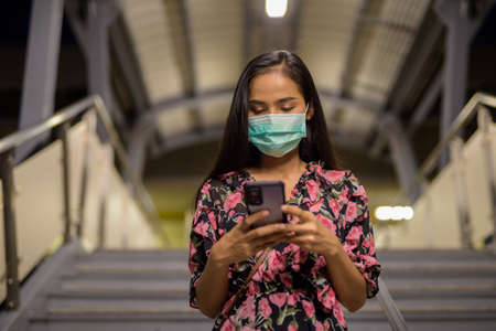 Portrait of woman wearing face mask for protection against virus while using mobile phone at night