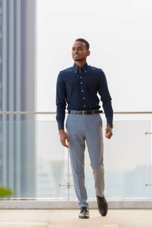 Portrait of handsome African businessman outdoors at rooftop in Bangkok, Thailand Archivio Fotografico