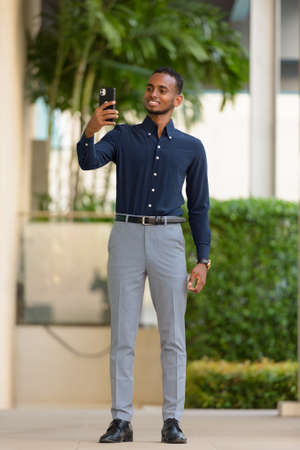 Portrait of handsome African businessman outdoors at rooftop in Bangkok, Thailand using mobile phone Archivio Fotografico