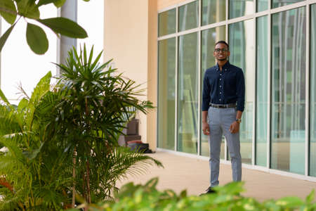 Handsome African businessman outdoors at rooftop garden full length shot