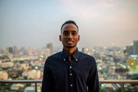 Portrait of handsome African businessman outdoors at rooftop smiling Archivio Fotografico