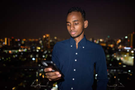 African businessman outdoors at rooftop using phone at night