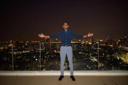 Full length shot of African businessman outdoors at rooftop during night with arms raised like winner