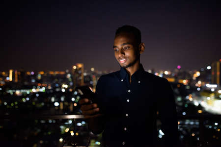 Happy African businessman outdoors at rooftop using phone at night