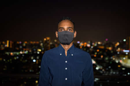 African businessman outdoors at rooftop wearing face mask at night