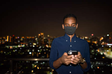 African businessman outdoors at rooftop wearing face mask at night while using mobile phone