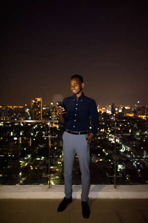 Full length shot of African businessman outdoors at rooftop during night using phone