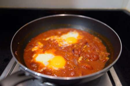 Shakshouka spicy tomato stew with chicken eggs traditional vegetarian dish horizontal shot
