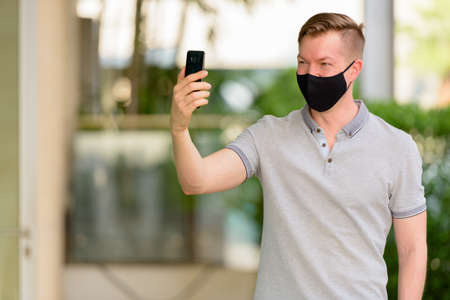 Man wearing face mask to protect from coronavirus Covid-19 outdoors Archivio Fotografico