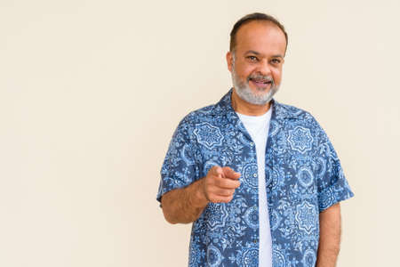 Portrait of handsome Indian man with gray beard against plain wall Standard-Bild