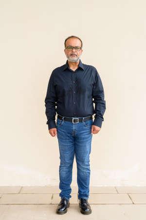 Full length portrait of handsome bearded Indian man against plain wall