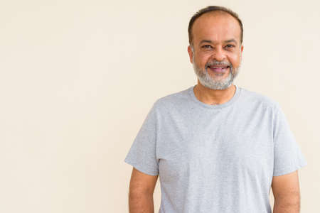 Portrait of happy bearded Indian man smiling against plain wall
