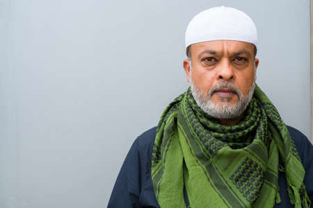 Portrait of handsome bearded muslim man against plain wall Standard-Bild