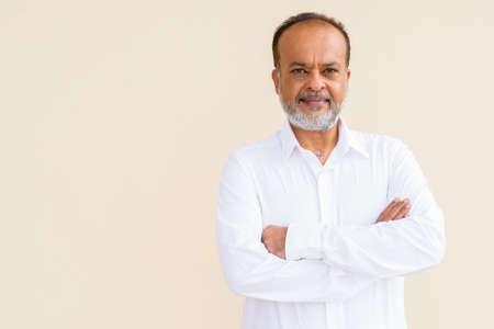 Portrait of handsome bearded Indian man against plain wall Standard-Bild