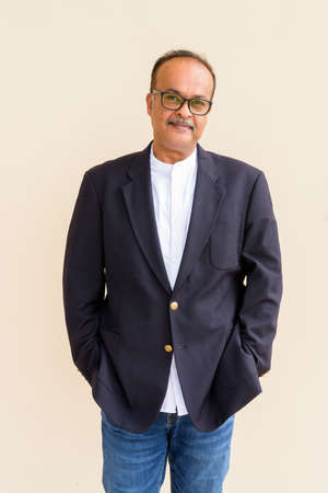 Portrait of handsome Indian businessman with mustache wearing hat against plain wall Standard-Bild